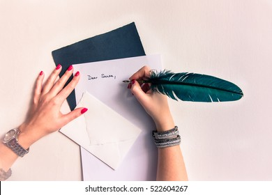 Dear Santa Claus Christmas card background - Woman hands with bright red nails and glossy jewelery wristband writing letter with green to teal blue feather quill pen