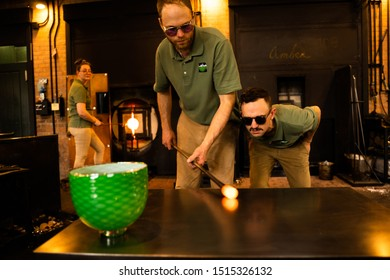 Dearborn, MI - May 17, 2019: Glass blower was demonstrating the art of glassblowing at Greenfield Village in Dearborn Michigan while his colleague scrutinize his work.