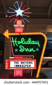 """DEARBORN, MI-JUNE 24, 2016:  Vintage """"Holiday Inn"""" motel neon sign from the 1950's.  There is a vintage Cadillac from the same time period in the background."""