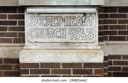 Dearborn, MI/USA: Sept 1, 2017 – Limestone carved name of Sacred Heart Church noting June 23 1929 construction date. Catholic parish of late Rep John Dingell Jr, longest serving member of US Congress.