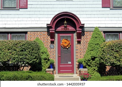 Dearborn, MI/USA: Sept 21, 2017 – Front entry door with arched millwork overhead, in Historic Ford District. Built in 1919, the trim is painted burgundy.  Seasonal autumn pumpkin wreath on door.