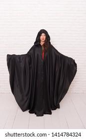 Death in black cloak symbol. Vampire in cloak sexy devil girl. Woman tempting vampire demon. Girl covered with cloak. Devil concept. Halloween masquerade. Halloween party. Damn pretty woman devil.