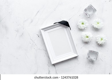 Death concept. Photo frame, mockup with black ribbon near flowers, candles on white stone background top view copy space