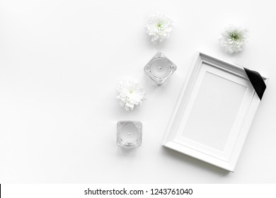 Death concept. Photo frame, mockup with black ribbon near flowers, candles on white background top view copy space