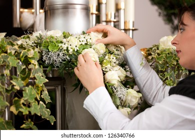death and dolor  - mortician on funeral with urn preparing the flowers