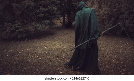 Death, Grim Reaper, with his scythe lurking in the woods in a haunted forest