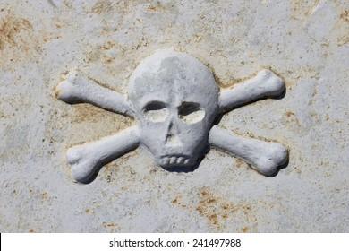 Death head on ancient tombstone in graveyard in Stari Grad, Hvar island, Croatia