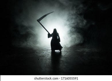 Death with a scythe on dark foggy toned background. Woman horror ghost holding reaper. Miniature artwork decoration. Halloween concept. Selective focus