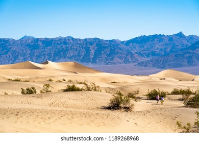 Death Valley, CA - June 11, 2018: Two people walk towards the crescent dune in Mesquite Flat Dunes in Death Valley California.
