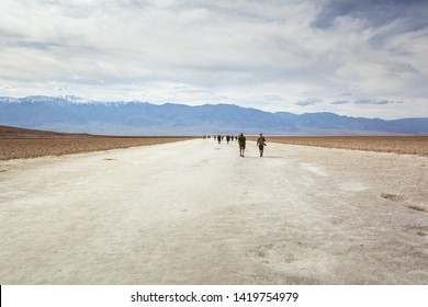 DEATH VALLEY, CALIFORNIA, USA - April 4, 2019: People visit the area of Badwater Basin at 282 feet below sea level, Badwater Basin is the lowest point in the USA.