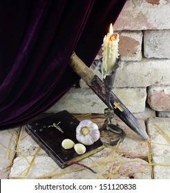 Death of a vampire: burning candle with Holy Bible, wooden cross and garlic