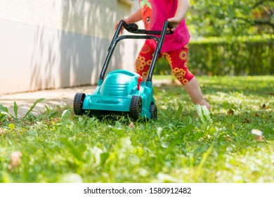Deatil of plastic toy lwn mower with child pushing it.