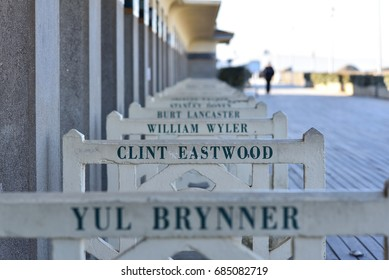 "DEAUVILLE (FRANCE) - NOVEMBER 30, 2016: barriers of beach huts ""Les Planches"" bearing the name of famous film-makers and actors"