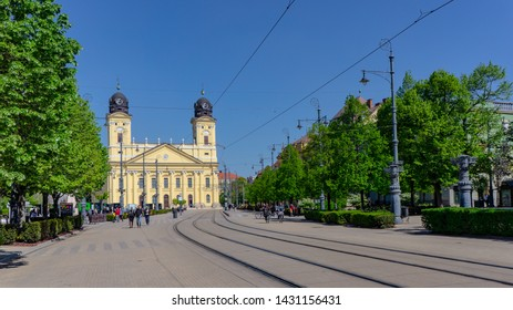 DEBRECEN, HUNGARY -04 19 2019 People walking and cycling on Kossuth Square in Debrecen.