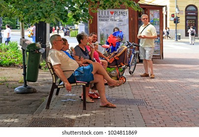 Debrecen, Hungary - June 30, 2017: people are resting on a bench outdoors in Debrecen, Hungary
