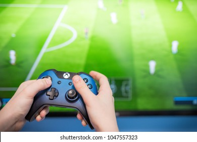 Debrecen, Hungary, Marc 11. 2018  View from the top on Xbox one s gamepad, game console, kid holding in his hands. Blurred background view and gaming concept. 2018 Fifa World Cup concept design