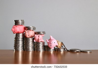 Debt concept, miniature piggy stuck between rolls of coins as ladder level and toy pigs fall on lowest step with money on wood table