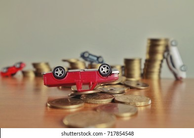 Debt concept, miniature red truck overturn upside down on pile of money and blur toy car on rolls ladder of coins on wood table in low light