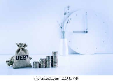 Debt financing / bad, unsecured consumer debt, financial concept : Debt bags, stacks of coins on a table, depicts rising in total interest expense a borrower should repay to a lender when paying late