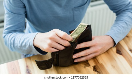 Debt and personal finances - closeup shot of a woman taking a single one US dollar bill from her wallet and looking at it.