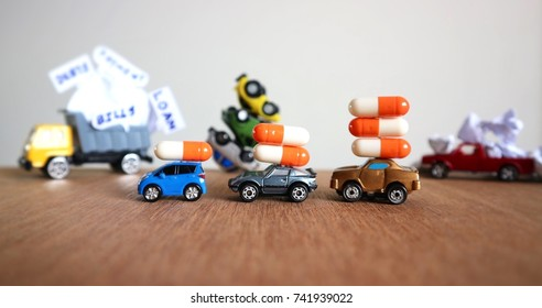 Debt and stress concept, miniature cars carry pills increasing and blur truck loaded crumpled paper with vehicles overturns upside down on wood table