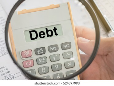 debt text on calculator and magnifier. concepts of debt management, calculation, debts control.