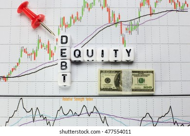 Debt-Equity written on white cube with candlestick chart background. Conceptual image for D/E ratio.