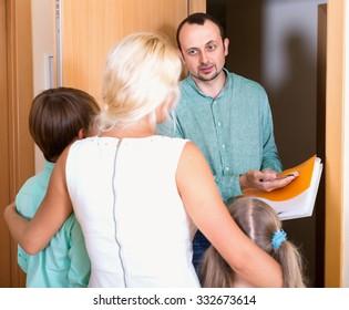 Debts collector standing at doorway in front of family