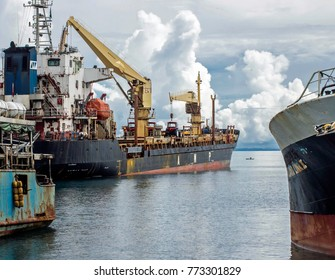 Dec 2017, Honiara Ports, Guadalcanal, Solomon Islands, an international vessel sits between two local inter island vessels while a little dug out canoe paddles past in the background