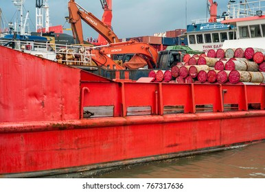 Dec 2017, Honiara, Solomon Islands, ships are parked one behind the other from fore- to background where some men with hardhats on watch the removal of containers