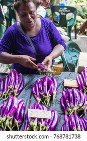 Dec 2017, Honiara, Solomon Islands, a vegetable seller wears a blouse which has about the same color as the product she sells it is a deep prple that looks like her eggplants