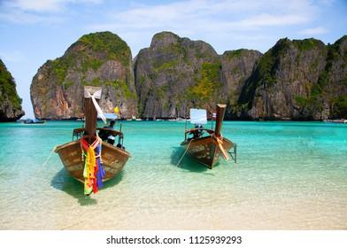 DEC 21, 2009 Krabi - Phuket, Thailand - Thai famous wooden long tail boat on white beach Phi Phi island and turqouise Andaman sea