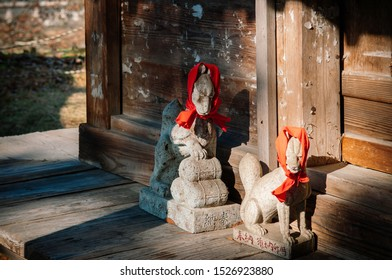 DEC 4, 2018 Aizu Wakamatsu, Japan - Kitsune Japanese Fox stone statue with red scarft and hat at shrine of Tsuruga castle - Close up face details - Japan god guard fox