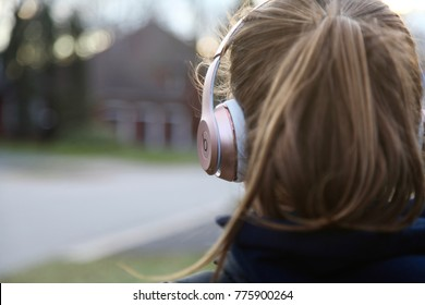 Dec 6th, 2017- Oakville, Canada: Teenage girl listening to rose gold beats head phones while walking home from school, focus on the headphones