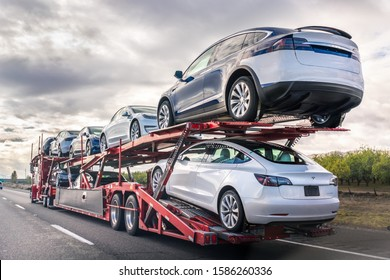 Dec 8, 2019 Bakersfield / CA / USA - Car transporter carries new Tesla vehicles along the interstate to South California, back view of the trailer
