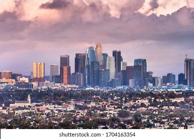 Dec 8, 2019 Los Angeles / CA / USA - Sunset view of the Financial District skyline and surrounding area with storm clouds covering the sky; Bank business logos visible on the skyscrapers exterior