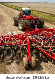 DECABRIST VILLAGE, SARATOV REGION, RUSSIA - 28 APRIL 2019: Sowing works on the wheat field. Planting complex - tractor and seeder mechanism