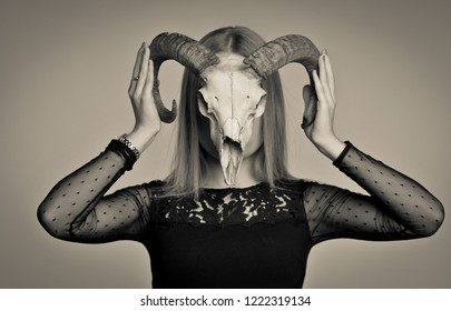 Decadence style image with girl and goats skull before her face. Girl with a horns on the head. Small black dress and big horns.