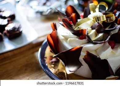Decadent chocolate and cream cake with pieces of dark chocolate on table with brownies in background conceptual celebration cake and elegant dessert photography