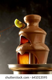 Decadent chocolate fondue fountain with a slice of kiwifruit on a fork being dipped into the cascading melted sauce