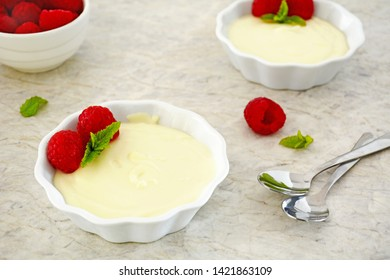 Decadent and delicious - creamy rich white chocolate custard with fresh ripe raspberries in little white dishes on textured background.