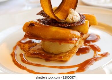 A decadent dessert of sliced banana, caramel, ice cream, and cinnamon.