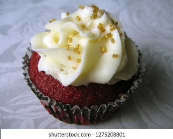 Decadent red velvet cupcake with cream cheese frosting and gold sugar garnish