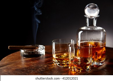 Decanter of alcohol by smoking cigar sitting in a round ashtray and two half filled glasses on a table in a dark room