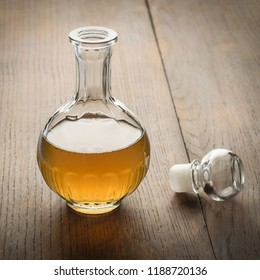 Decanter of apple cider vinegar on a wooden table.