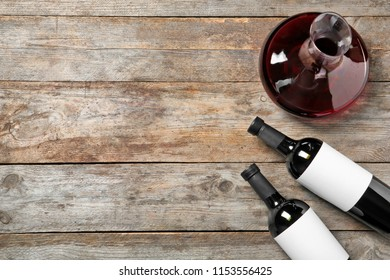 Decanter and bottles with red wine on wooden background, top view