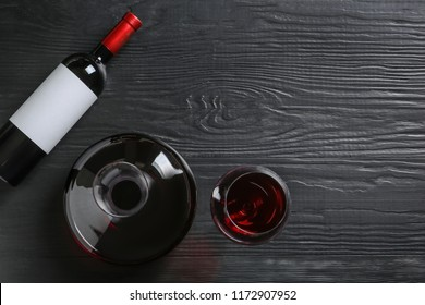 Decanter, glass and bottle with red wine on wooden background, top view