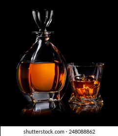 Decanter and glass of whiskaey on black background