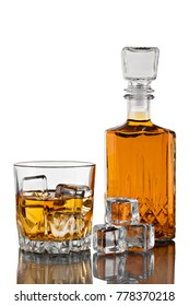 Decanter, a glass of whiskey with ice. on white background with reflection