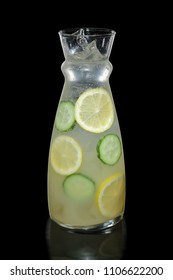 Decanter with lemon and cucumber lemonade isolated on black